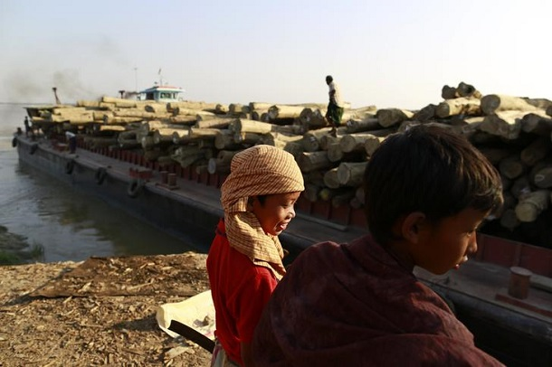 Boys stand on a jetty as a ship loaded with teak logs arrives at National Village timber yard by the Bago river in Yangon February 2, 2014. Picture taken February 2, 2014. To match story MYANMAR-FOREST/ REUTERS/Soe Zeya Tun (MYANMAR - Tags: BUSINESS SOCIETY)